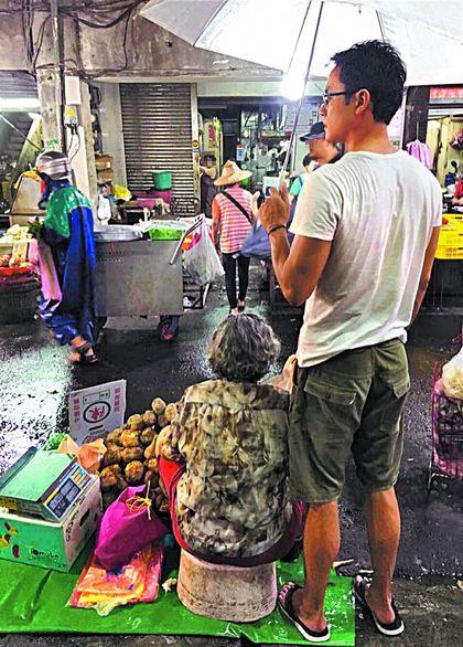 明道的媽媽(左)坐在板凳賣地瓜,明道撐傘站在一旁。
